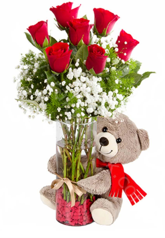 Büyük aşklar sonsuzdur. Cam vazo içerisinde 7 adet kırmızı güllerden oluşan arajman, 1 adet peluş ayıcık, boy 15 cm
